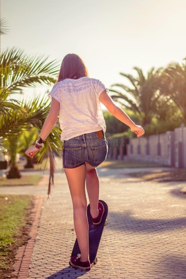 Tylny widok dziewczyny jazda w deskorolka outdoors fotografia royalty free