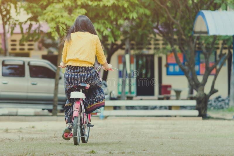 Tylny widok ?e?ski nauczyciel jedzie bicykl uczy? uczni fotografia royalty free