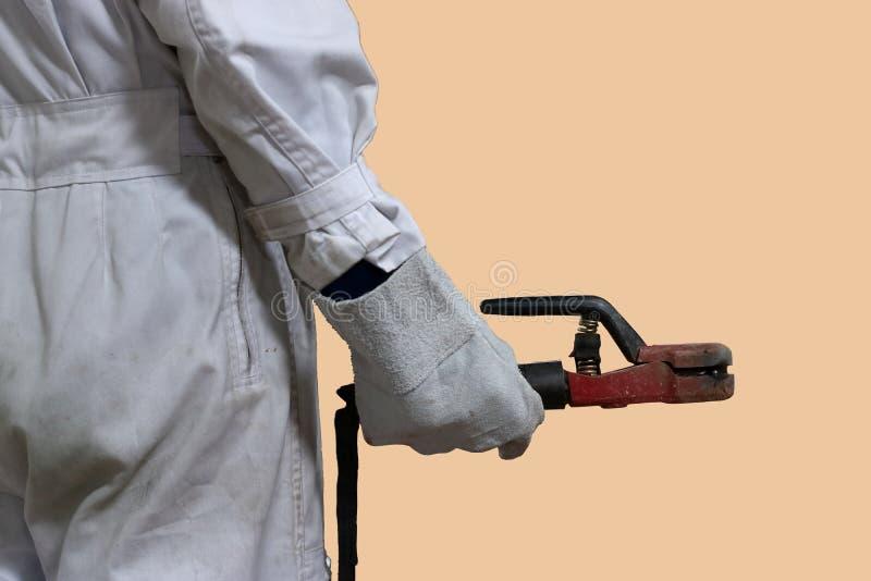 Tylny widok fachowy spawacza pracownik w bielu munduru mienia łuku spawalniczej pochodni w jego rękach na tle obrazy royalty free