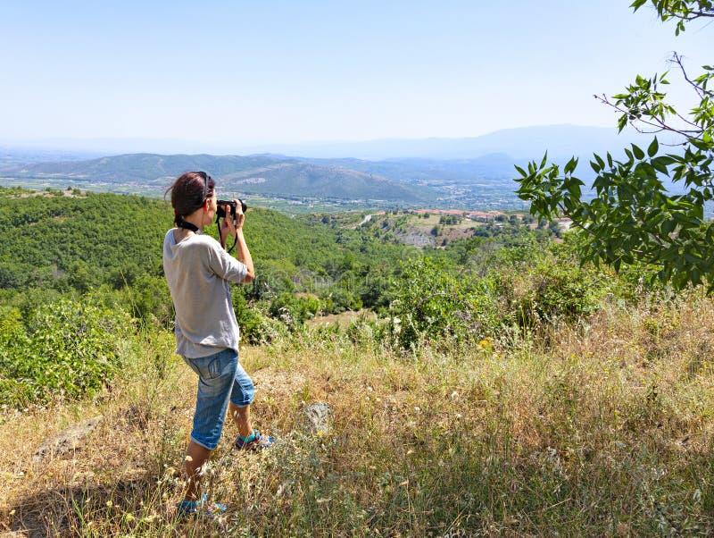 Tylny widok kobieta fotograf bierze obrazki dolina z górami obraz stock