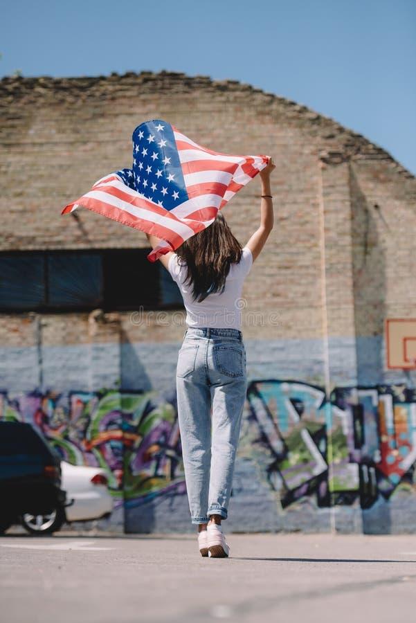 tylny widok kobieta stoi na ulicie z flaga amerykańską w rękach, 4th Lipiec fotografia stock