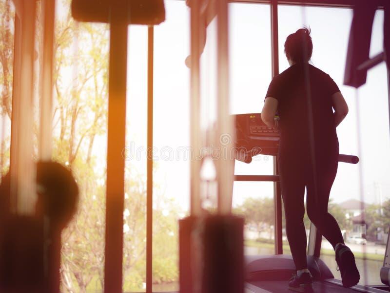 Tylny widok kobiety atlety bieg na Działającej maszynie w gym, ćwiczenie dla zdrowie zdjęcie stock