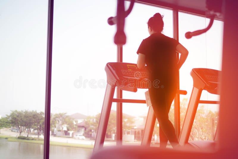 Tylny widok kobiety atlety bieg na Działającej maszynie w gym, ćwiczenie dla zdrowie obraz royalty free