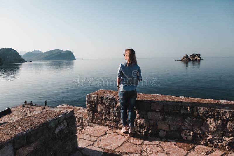 Tylny widok kobiety g??wkowanie samotnie, dopatrywanie i morze z horyzontem w tle, Montenegro zdjęcia stock