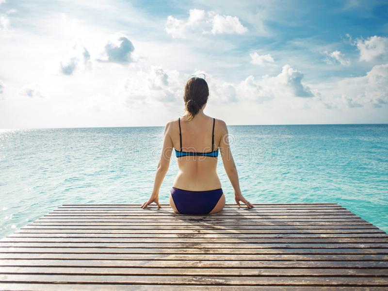 Tylny widok kobiety obsiadanie na tle piękny niebo i morze obraz stock