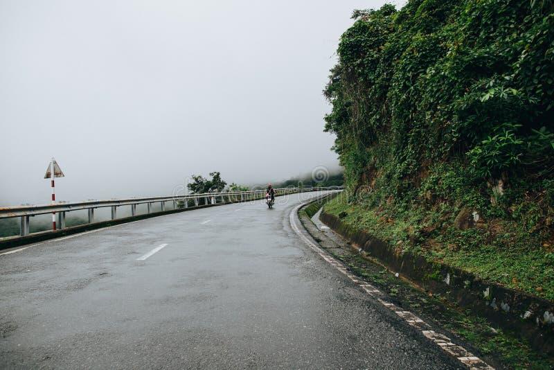 tylny widok ludzie jedzie motocykl na halnej drodze w Hai Van Przechodzący, Wietnam obraz royalty free