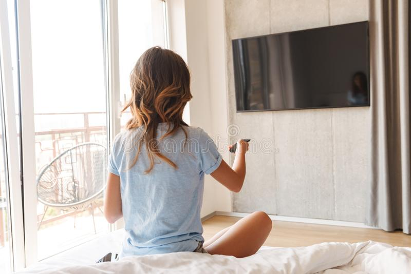 Tylny widok młodej kobiety obsiadanie na łóżku obrazy stock