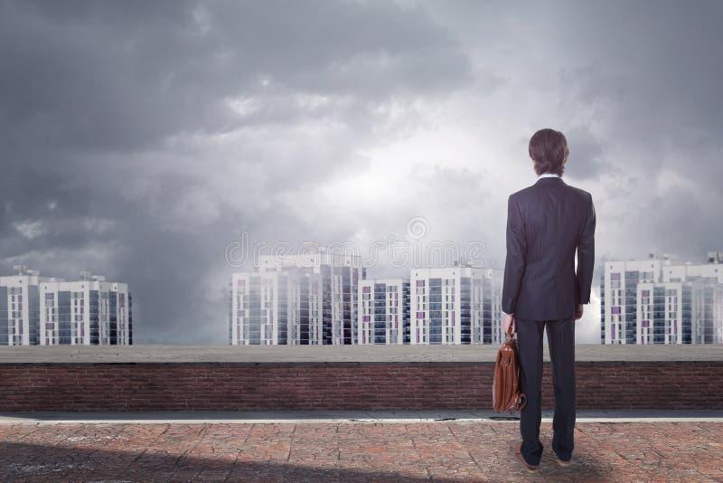Tylny widok młody biznesmen patrzeje miasto z kopii przestrzenią na dachu fotografia royalty free