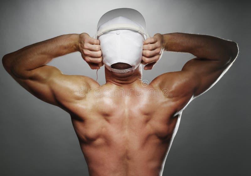 Tylny widok Mięśniowy mężczyzna z nakrętką i hełmofonami obraz stock