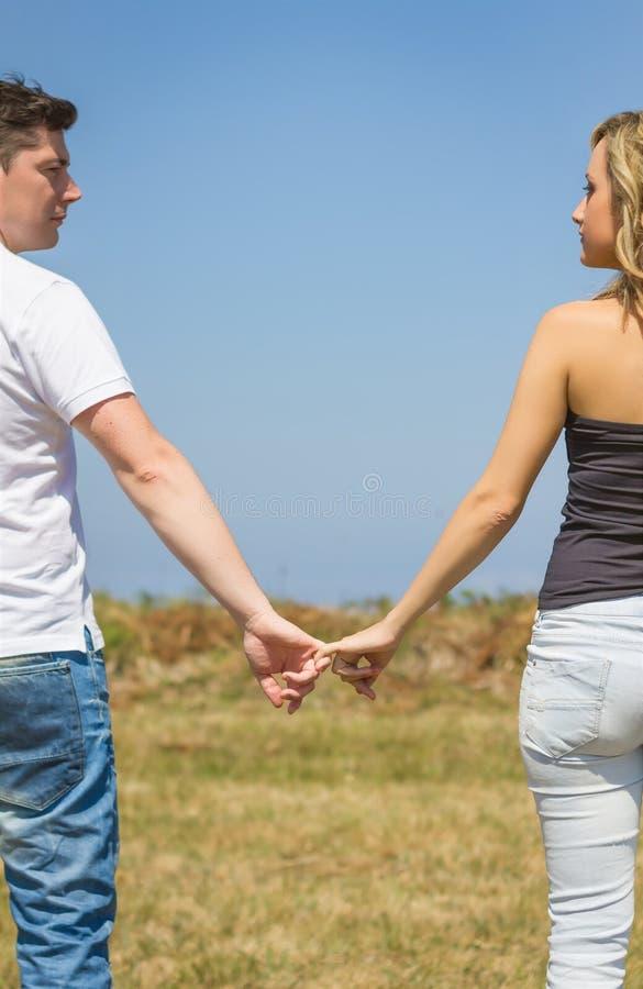 Tylny widok miłości pary mienie wręcza outdoors zdjęcia stock