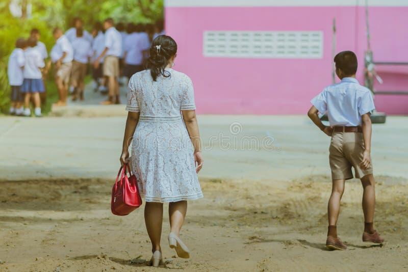 Tylny widok nauczyciel i uczni chodzi? i?? studiowa? przy sal? lekcyjn? zdjęcia stock