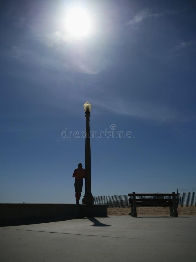 Tylny widok opiera na latarni ulicznej przy dniem mężczyzna fotografia stock