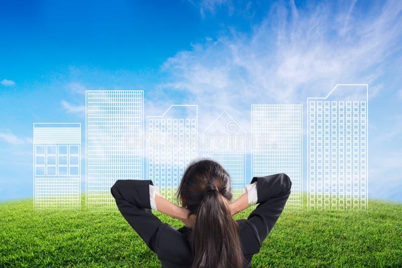 Tylny widok patrzeje nakreślenia projekt budowlany na natury tle bizneswoman obraz stock