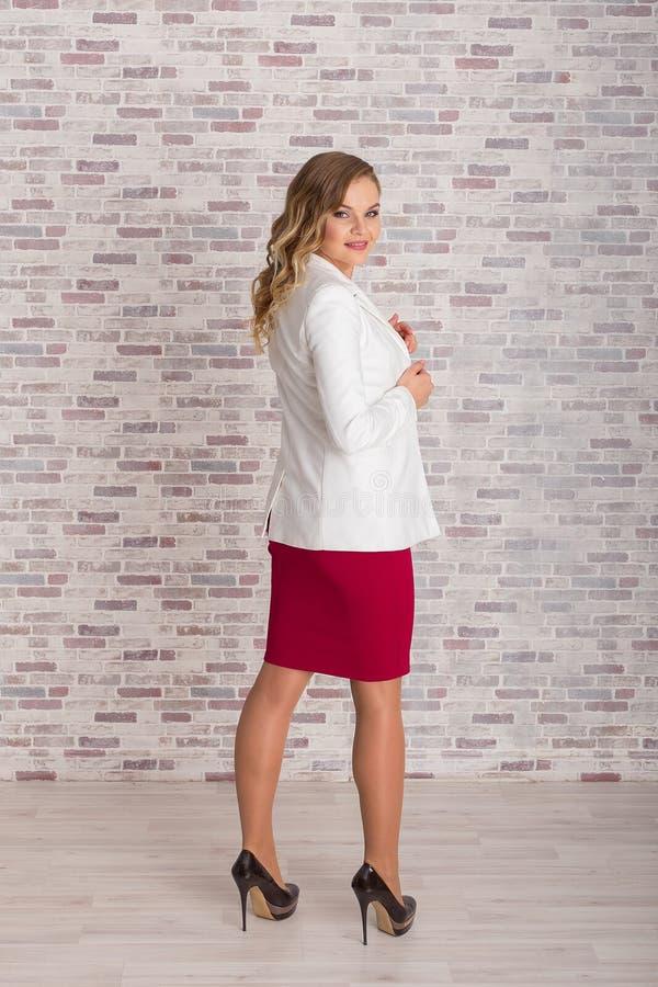 Tylny widok piękna biznesowa kobieta w pełnym przyroscie w czerwieni sukni w białym kostiumu i obrazy stock