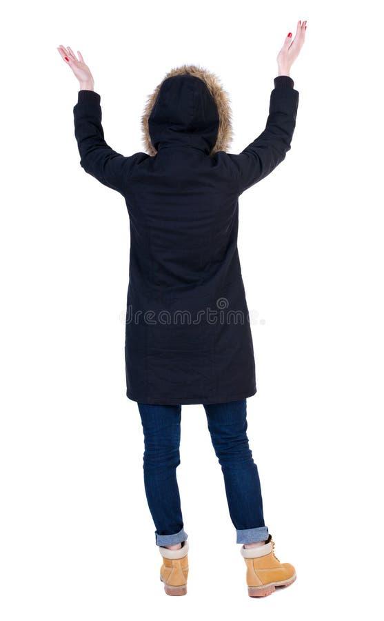 Tylny widok Piękna kobieta patrzeje ścianę i chwyty w parka zdjęcie stock