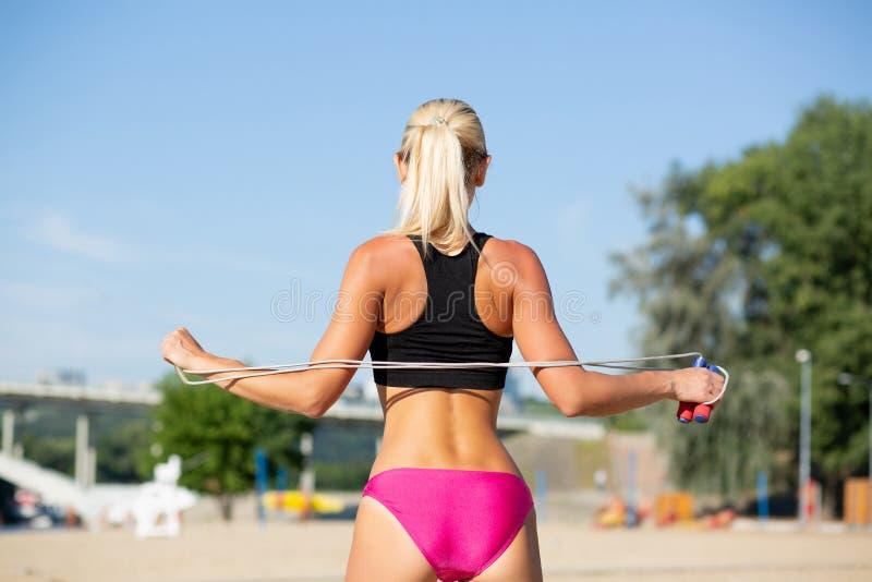 Tylny widok piękna nikła dziewczyna robi rozciąganiu opracowywa z skok arkaną przy plażą obraz royalty free