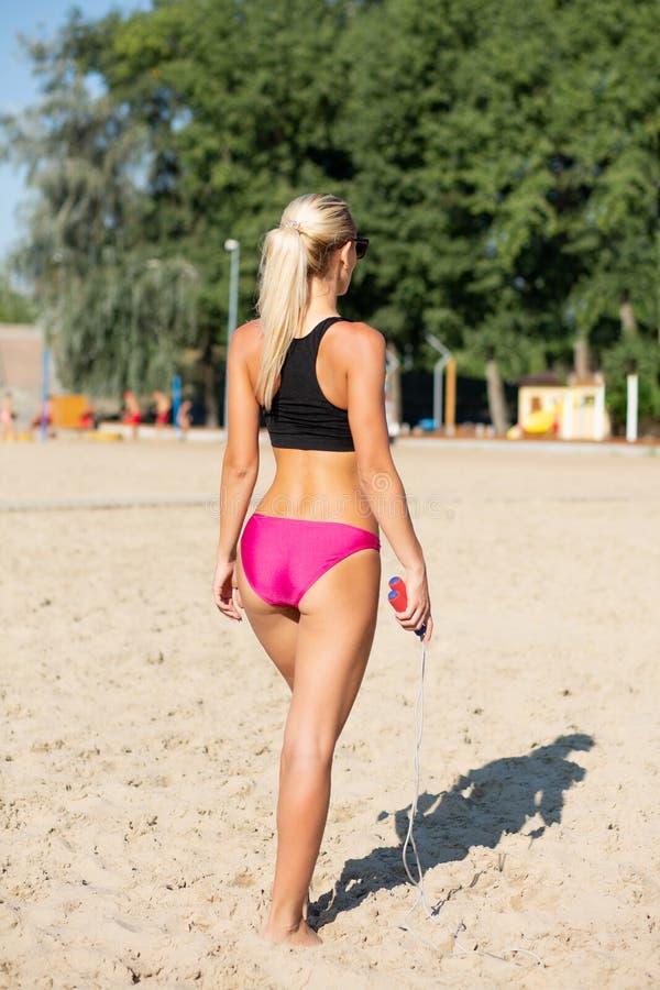 Tylny widok piękna sprawności fizycznej dziewczyna trenuje z skok arkaną przy plażą fotografia stock