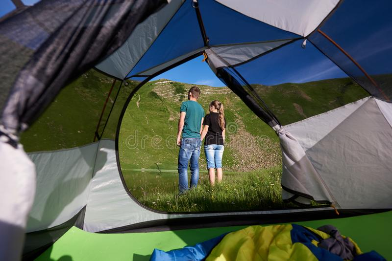 Tylny widok potomstwa dobierać do pary odpoczynkowego pobliskiego camping w górach obraz stock