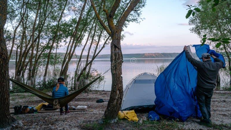 Tylny widok relaksuje na oliwnym hamaku mi?dzy dwa drzewami cieszy si? widok przy jeziorem w lato wiecz?r dziewczyna m??czyzna us zdjęcia stock
