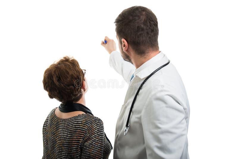 Tylny widok samiec doktorski wskazywać żeński pacjent z markierem obraz stock