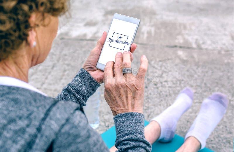 Tylny widok starsza kobieta używa smartphone obrazy royalty free