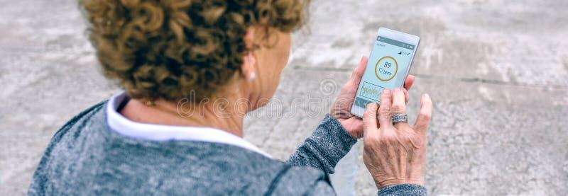 Tylny widok starsza kobieta używa smartphone zdjęcie royalty free