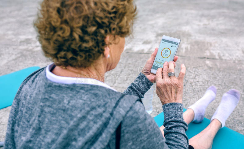 Tylny widok starsza kobieta używa smartphone fotografia royalty free