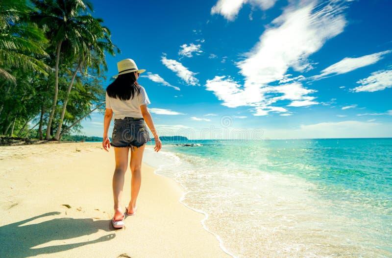 Tylny widok szczęśliwa młoda kobieta chodzi przy piaskiem w przypadkowego stylu modzie i słomianego kapeluszu odzieży sandały wyr fotografia stock