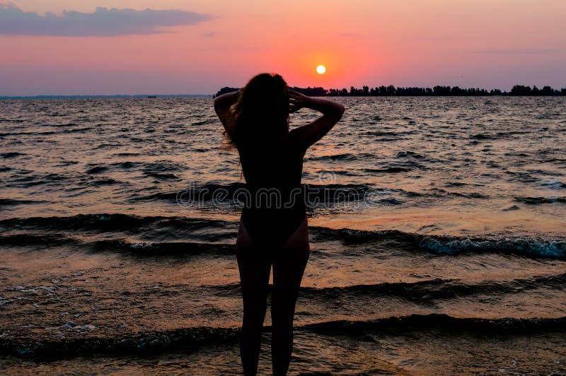 Tylny widok szczupła kobiety postać w swimsuit pozycji, korygować włosiany i patrzeć zadziwiającego wschód słońca, obrazy stock