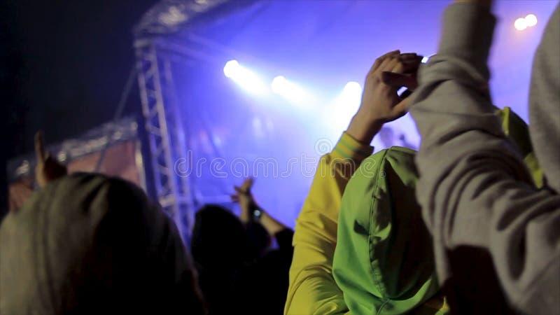 Tylny widok tłum ludzie przy koncertem footage Sylwetki koncertowy tłum przed jaskrawą sceną zaświecają zdjęcie royalty free