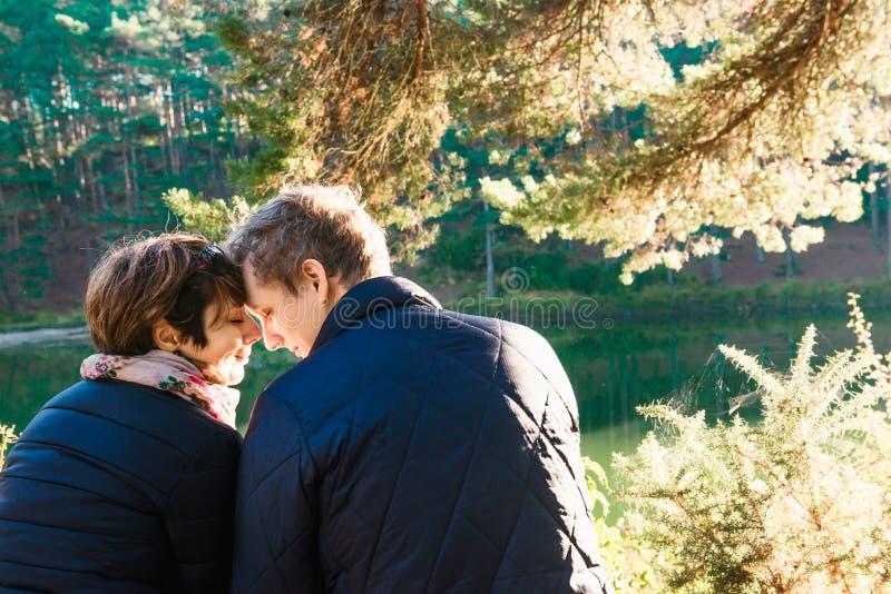 Tylny widok uroczy para mężczyzna, kobieta siedzi blisko i lasowego jeziornego przytulenia i relaksować Miłość emocji Plenerowi p obrazy stock
