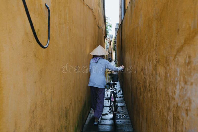 tylny widok wietnamczyk kobieta w tradycyjnym kapeluszowym przewożenie bicyklu na wąskiej ulicie w Hoi, Wietnam fotografia stock