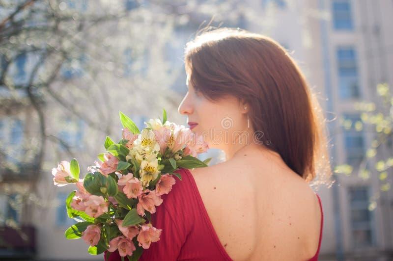 Tylny widok zadziwiająca i piękna młoda kobieta trzyma dużego bukiet kolorowi kwiaty outdoors blisko budynków dalej obrazy stock