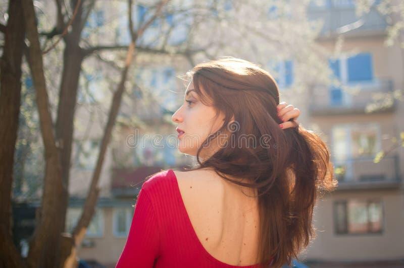 Tylny widok zadziwiająca rozochocona dziewczyna z ślicznymi zmysłowymi wargami cieszy się wiosnę w mieście podczas słonecznego dn fotografia royalty free