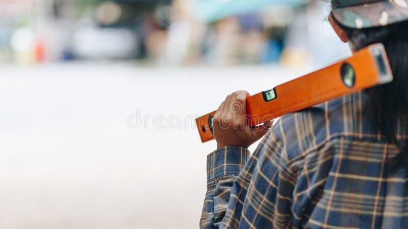 Tylny widoku pracownik budowlany z poziomem obrazy stock