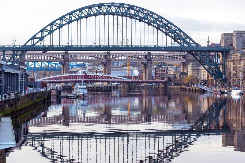 Tyne Bridge mirrored in the River Tyne, Newcastle, UK with Swing, Queen Elizabeth II and High Level bridges in the. Newcastle, England - November 09 2019: Tyne stock image