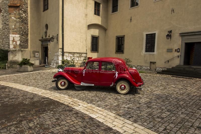Tyniec, Krakow, Poland, August 3, 2019: Old, antique red car used to transport newlyweds at the wedding, royalty free stock photography