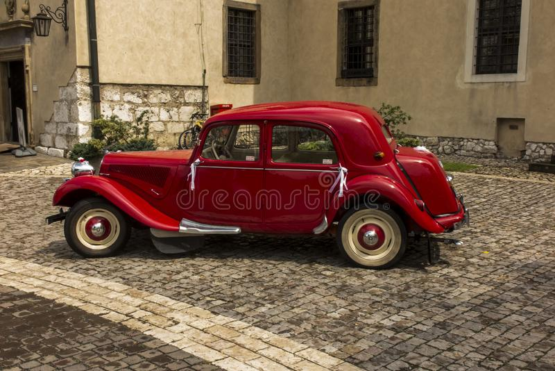 Tyniec, Krakow, Poland, August 3, 2019: Old, antique red car used to transport newlyweds at the wedding, royalty free stock photo