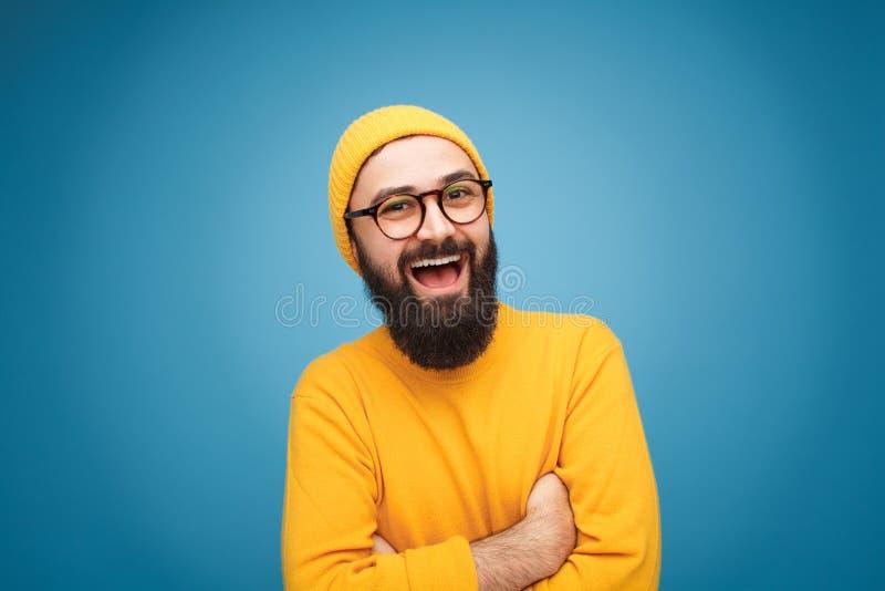 Type à la mode de sourire sur le fond bleu photo libre de droits