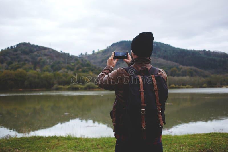 Type élégant de hippie avec un sac à dos sur sa photo de prise arrière au téléphone de cellules photos libres de droits