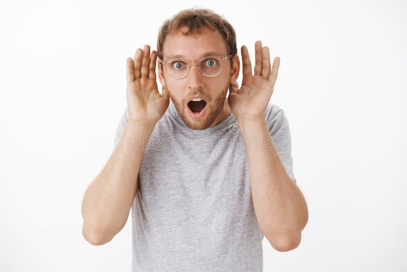 Type étant impressionné des rumeurs écartant autour du bureau Surprised a amusé le jeune mâle beau dans le T-shirt gris et photos libres de droits