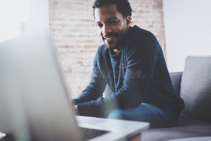 Type africain barbu gai travaillant sur l'ordinateur portable tout en reposant le sofa à son endroit moderne de bureau Concept de photographie stock libre de droits