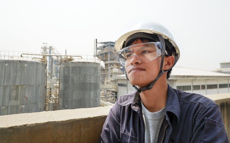 Type asiatique portant un fonctionnement de casque dans une grande usine industrielle vérifiant le processus de fabrication photos stock