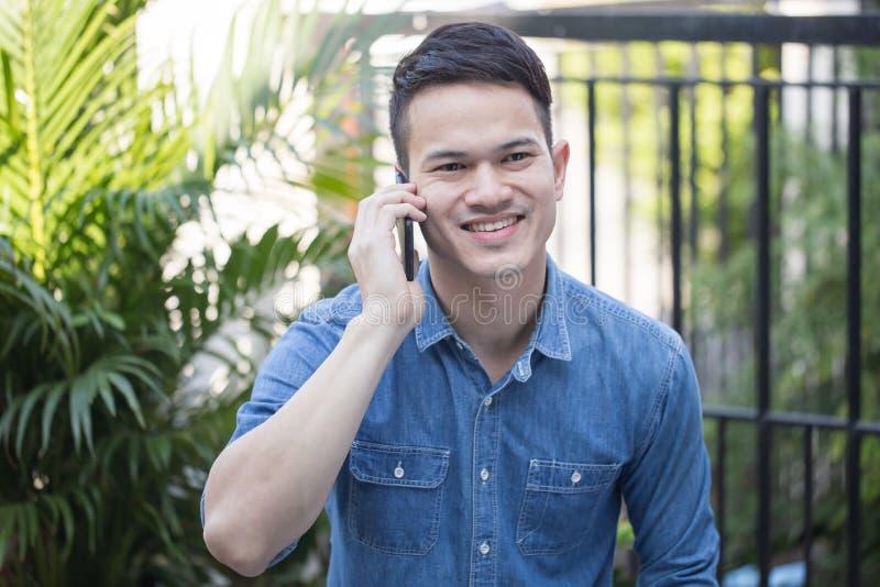Type asiatique portant une robe confortable parlant sur le smartphone, sourires beaux de type heureux de parler image libre de droits