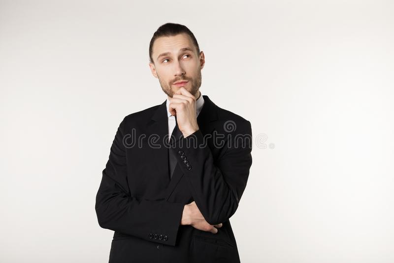 Type attirant, professeur avec les cheveux élégants et barbe dans le costume noir tenant son menton et regardant pensivement de c photographie stock libre de droits