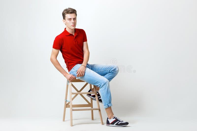 Type aux cheveux foncés beau calme utilisant la chemise rouge et les blues-jean se reposant sur le tabouret en bois au-dessus du  photo stock