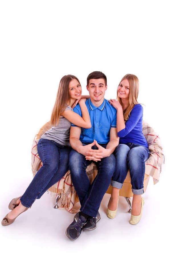 Type avec deux filles s'asseyant sur le divan photos stock