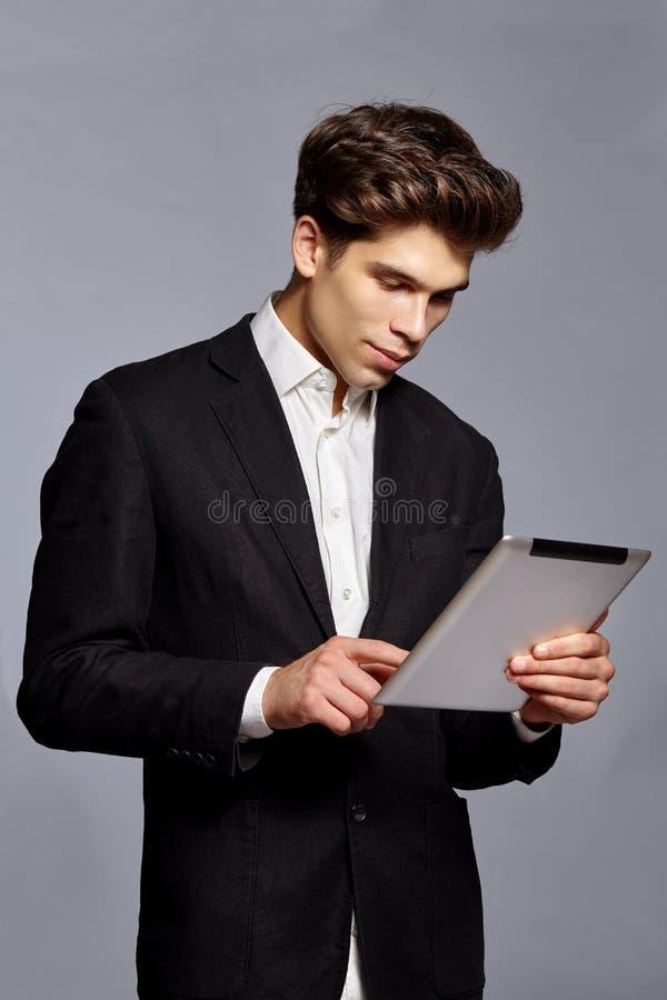 Type avec la coiffure tenant le comprimé et travaillant à lui photographie stock