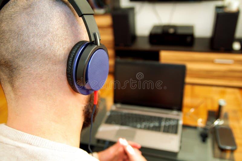 Type avec la musique de écoute d'écouteurs sur l'ordinateur portable dans le salon photos libres de droits