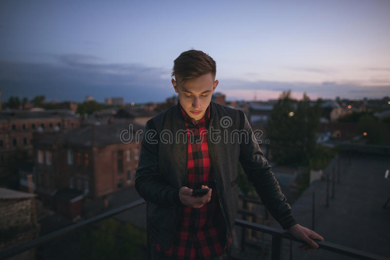 Type avec le téléphone portable sur le contexte de ciel photo stock